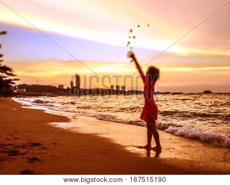 Asian girl playing sand cast on the beach nice shot in sunset time at Pattaya Thailand Focus select at sand and wave around are blur concept funny in her dream color is bright fantasy style.