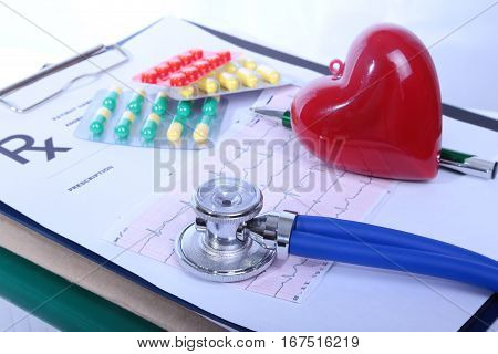 Closeup of a pils, red heart. stethoscope, pen on an rx prescription