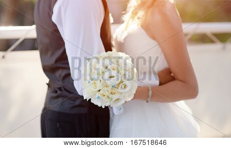 White roses wedding bouquet in bride's hand near groom