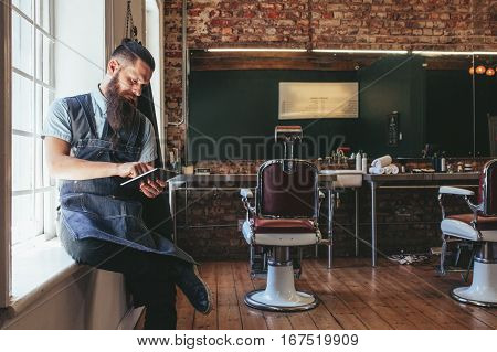 Barber Organizing His Business Using Digital Tablet