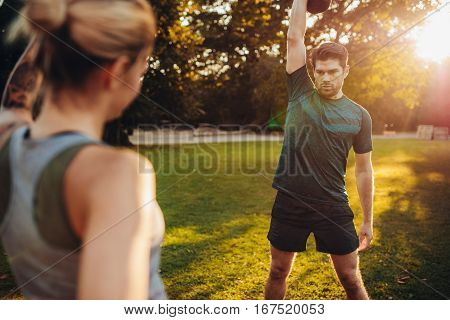 Healthy Man Exercising With Personal Trainer In Park