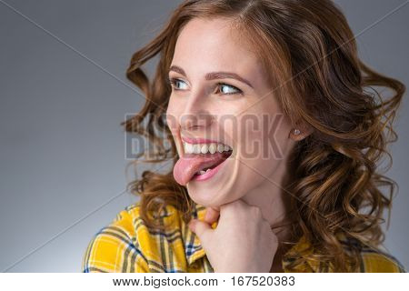 beautiful young woman in a yellow shirt expresses emotions show tongue on a gray background