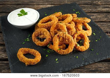Fried Breaded Onion Rings with sauce on stone board.