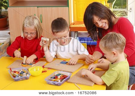 teacher and three preschoolers playing with wooden blocks