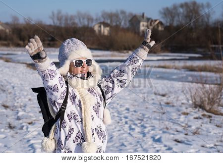 Fashionable beautiful little girl walking by the river on a sunny winter day. Portrait of a stylish little girl on the walking with winter clothes and sunglasses. Caucasian stylish little girl