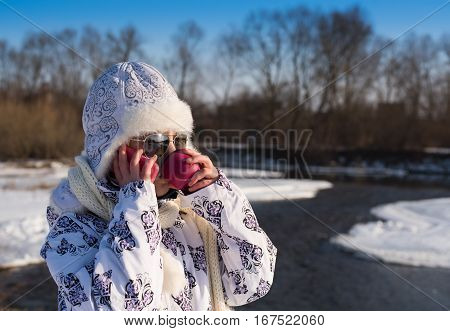 Little girl using her phone on a sunny winter day. Smiling little girl with a pink cup of hot drink. Glamour little girl talks on phone. Caucasian stylish little girl in winter clothes and sunglasses walking outdoor.