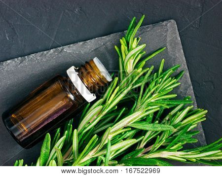 Rosemary essential oil in dark glass bottle and fresh rosemary on dark background. Top view or flat lay