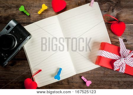 Love letter notepad with photocamera red plush hearts toys and clothespins-tabs in the form of hearts on wooden table top view copy space