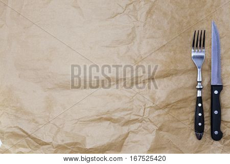 The background for the menu. Wrapping paper and a fork and a steak knife. Is used to create a menu for a Steakhouse. Good background to create restaurant menus, cafes bars.