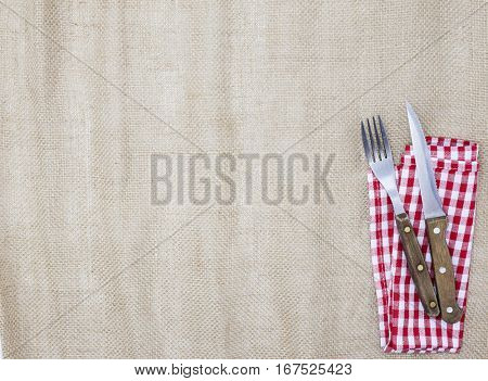 The background for the menu. Canvas tablecloth, fork, knife and napkin for steaks. Is used to create a menu for a steak house.