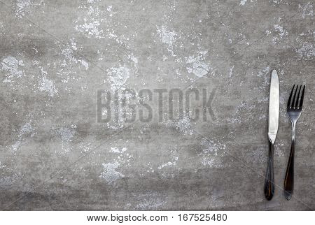 Menu.Stone table with fork and knife, a Good background for creating restaurant menus, cafes bars.