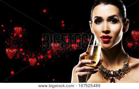 romantic woman with golden makeup and nailpolish. Big gold fashion necklace. Black isolated background. Holding glass of champagne. Red love Valentines Day hearts.