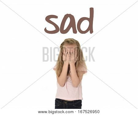 English language learning vocabulary school card with word sad and sweet young little schoolgirl covering her face with her hands crying sad victim of bullying at school isolated on white