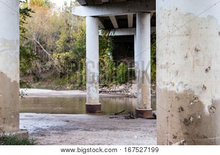 Shore and river scene underneath a busy highway.