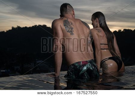 Romantic sensual couple alone in infinity swimming pool over beautiful tropical background