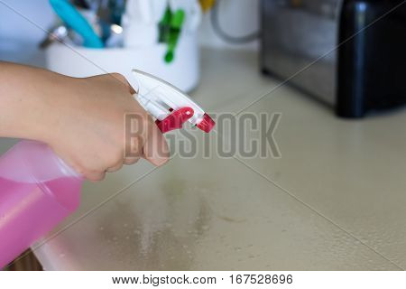 Woman spraying houshold cleaner on kitchen counters.