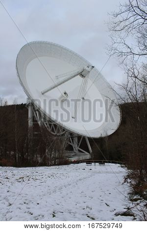 Radiotelscope Effelsberg in the winter of 2017, the largest Radiotelscope in the world in Effelsberg in the Ahrgebirge, in the foreground snow slope with visitor platform, two benches, railings and two marvelous persons, in the background the forest