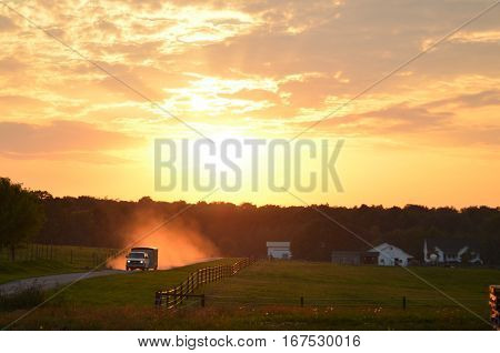 Van kicking up dust driving down an Amish country drive at Sunset