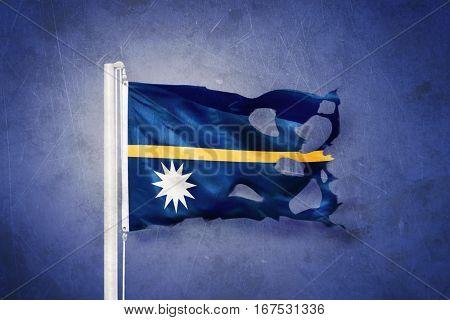 Torn flag of Nauru flying against grunge background.