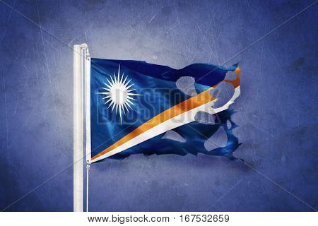 Torn flag of Marshall Islands flying against grunge background.