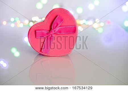 Pink gift box in the form of heart on the background illumination
