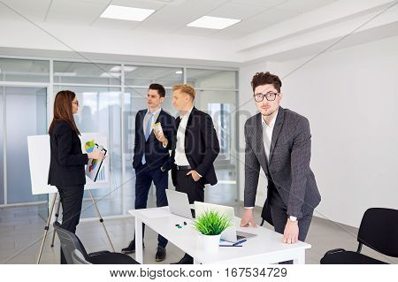 Businessman with glasses on the background of business people in a modern office.