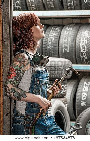 Photo of a beautiful redhead female mechanic with holding a welding torch.