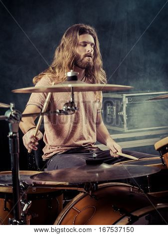 Photo of a young male drummer with long hair playing his drum set. Filtered for vintage look.