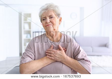 Elderly woman having heart attack at home