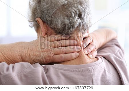 Elderly woman suffering from neck pain, closeup