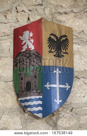 coat of arms of the last name baeza on a wall of stone as background