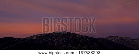 A vivid sunset is captured over distant hills.