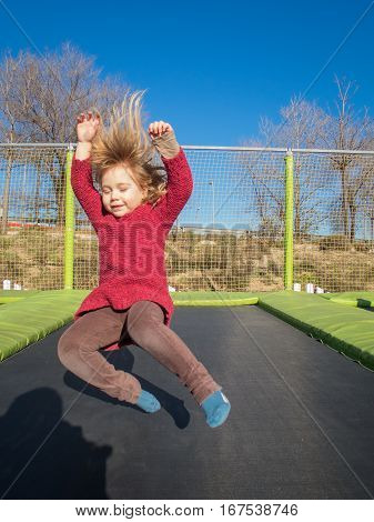 Happy Little Child Jumping On Trampoline