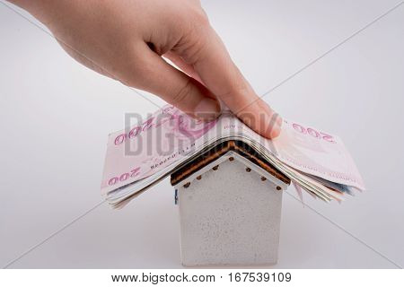 Hand Holding Turkish Lira Banknotes On The Roof Of A Model House