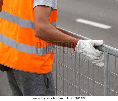 Worker With Orange High-visibility Vest While Moving The Iron Fe