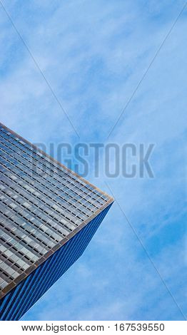 Partial view of a corporate skyscraper from the bottom in front of cloudy sky toned shot