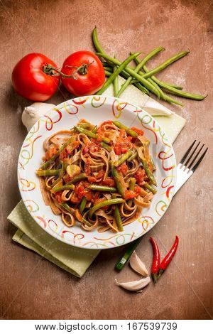 spicy integral tagliatelle with green beans and tomato sauce