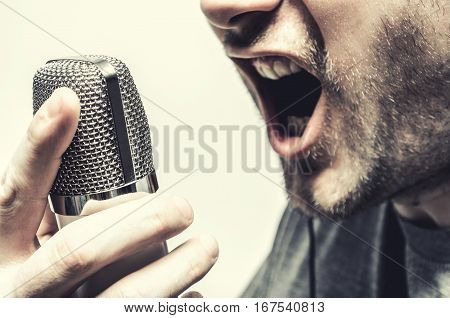 a man sings a song using a condenser microphone