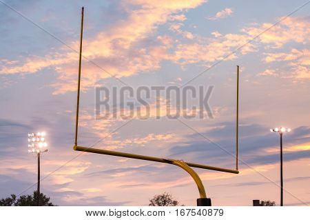 Yellow american football goal posts at school field against the lights and clouds of setting sun