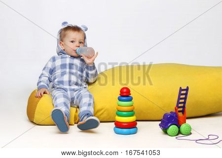 Shot of a little baby boy playing with some toys and drinking from a sippy cup.