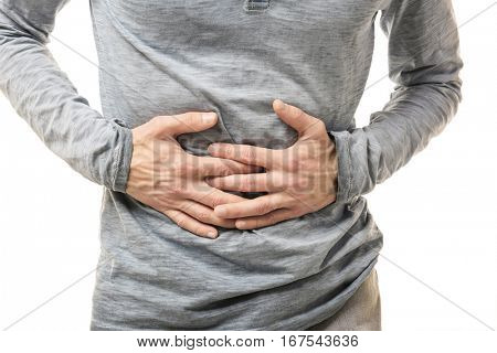 Man suffering from abdominal pain on white background, closeup