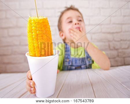 Cute boy holdind boiled sweet corn in cup on white bricks wall background.