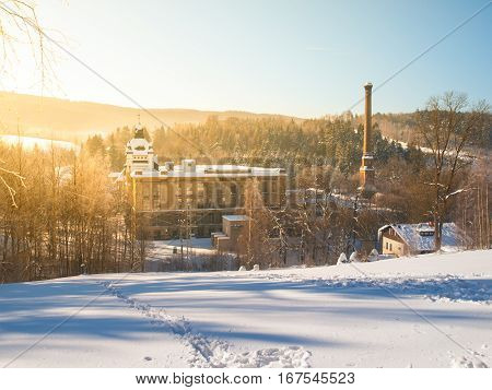 Old textile factory called Klaster, Monastery, with high chimney in winter time, Tanvald, Northern Bohemia, Czech Republic, Europe.