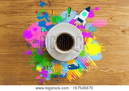 Top view of wooden desktop with coffee cup and colorful rocket ship sketch. Creative start up ideas