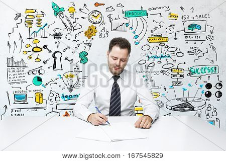 Attractive young man doing paperwork at workplace with colorful business sketch. Product placement concept