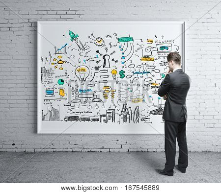Thoughtful businessman in interior looking at whiteboard with business sketch. Financial growth concept