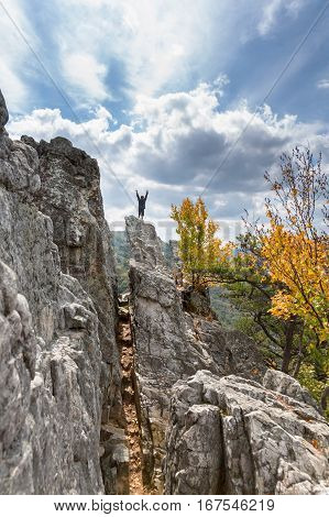 Young climber reaches the summit of the rocky granite mountain top of Seneca Rocks in West Virginia