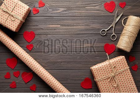 Flat lay composition in rustic style on Valentine's Day, a birthday or Mother's Day with gifts, scissors, wrapping paper and twine. Dark wooden background with woolen hearts. Flat lay. Top view.