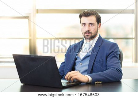 Portrait of successful corporate businessman in bright modern office with laptop computer looking at camera. Business and entrepreneurship concept.