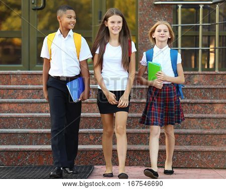 Cheerful teenagers with backpacks and notebooks leaving school